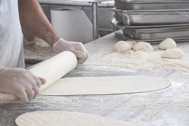 Männliche hände, die teig für pizza auf tisch vorbereiten.