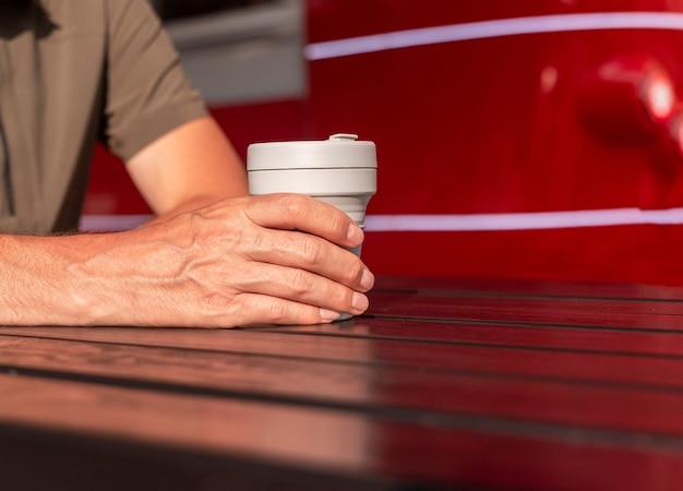 Männliche hände, die wiederverwendbare öko-kaffeetasse zum mitnehmen in den händen über einem hölzernen straßentisch auf dem gericht mit ...