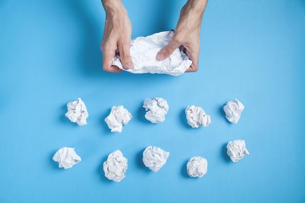 Männliche hände, die zerknittertes papier auf blauer wand halten