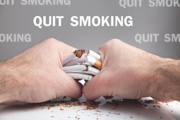 Männliche hände, die zigaretten brechen