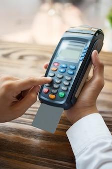 Männliche hände drückt knöpfe auf kreditkartenleser