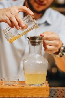 Männliche hände gossen die trockenen blätter des grünen tees in transparentem glas