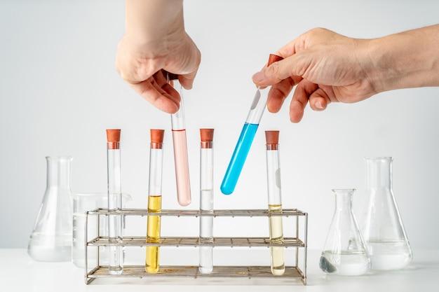 Männliche hände halten die reagenzgläser des chemielabors und stecken sie wieder in die röhrchenhalter