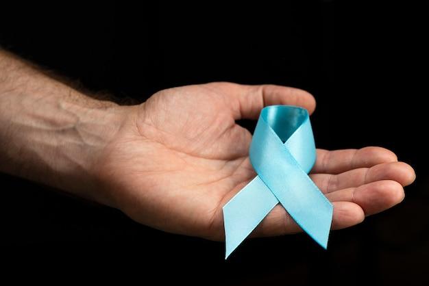 Männliche hände halten ein blaues band auf einer dunklen oberfläche