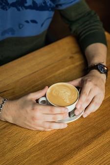 Männliche hände halten eine tasse cappuccino-kaffee, holztisch