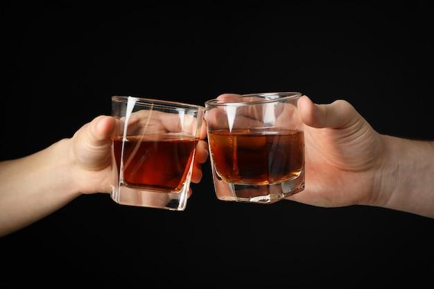 Männliche hände halten gläser whisky auf schwarzem hintergrund, nahaufnahme. prost