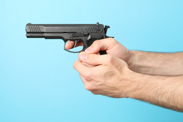 Männliche hände halten schwarze pistole auf blau
