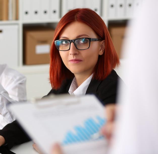 Männliche hände halten zwischenablageblock mit finanzstatistik im büro