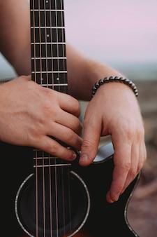Männliche hände hautnah auf schwarzer akustikgitarre. draussen
