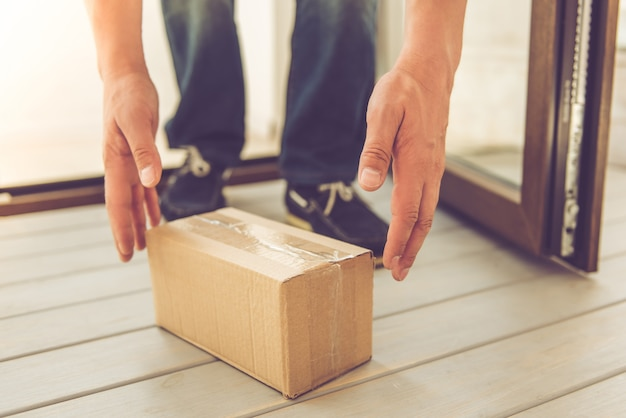 Männliche hände heben ein paket, das auf dem boden steht