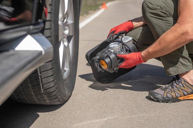 Männliche hände im handschuh und tragbare reifenpumpe zum aufpumpen des autoradreifen-luftkompressors mit ...