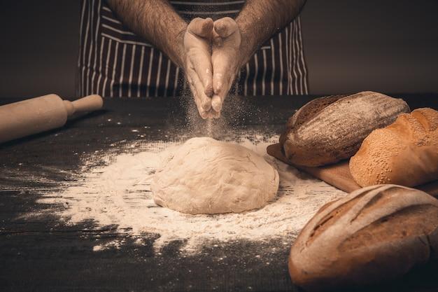 Männliche hände kneten den teig. koch kocht brot und brötchen