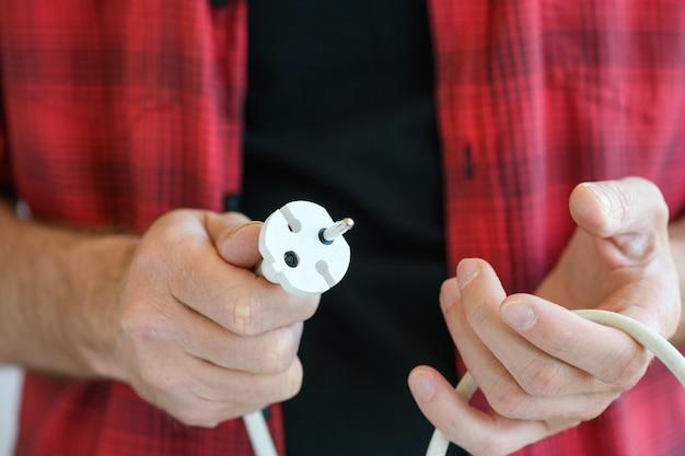 Männliche hände mit gebrochenem europäischem doppeltem verlängerungsstecker zum reparieren, werfen oder ändern, elektronik-master-konzept