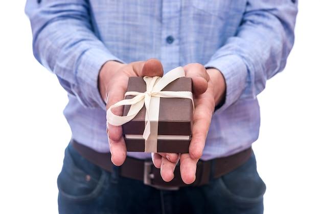 Männliche hände mit geschenkbox lokalisiert auf weiß
