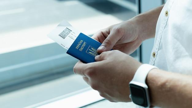 Männliche hände mit reisepass und tickets auf dem hintergrund des flughafens