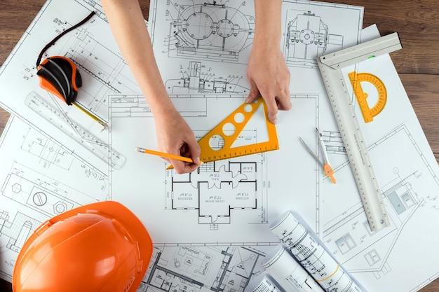 Männliche hände, orange sturzhelm, bleistift, architekturbauzeichnungen, maßband.