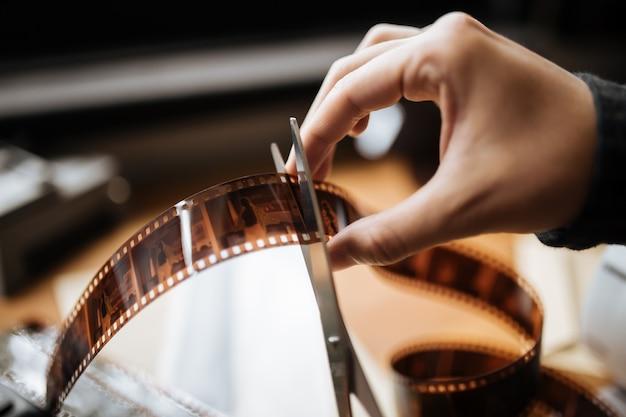 Männliche hände schneiden vintage film 35mm