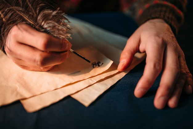 Männliche hände schreiben mit einer feder auf vintage-papier
