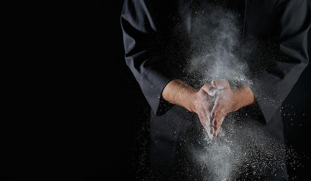 Männliche hände und spritzer von weißem weizenmehl auf einem schwarzen hintergrund