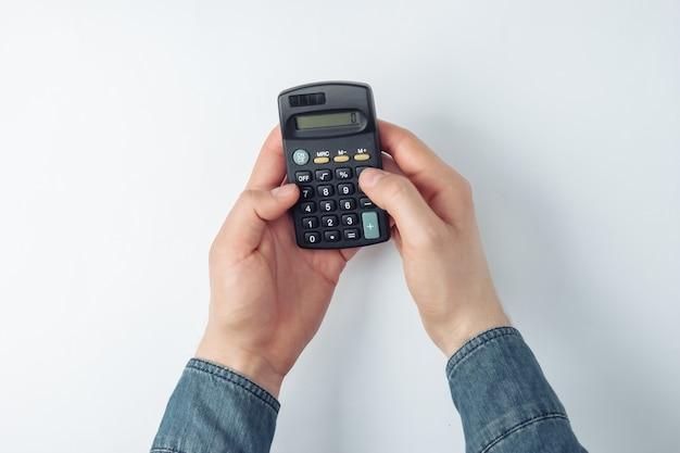 Männliche hände zählen auf einem taschenrechner auf weiß