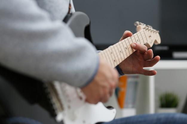 Männliche hände zu hause spielen und stimmen die e-gitarre, die an musik teilgenommen wird, verwirklicht das hören, musiknotation genießend, große konzeptnahaufnahme
