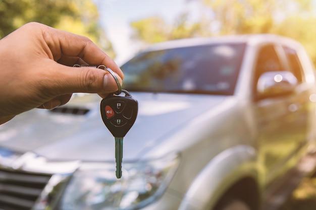 Männliche haltene autoschlüssel mit auto auf hintergrund
