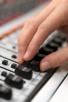 Männliche hand auf steuerfader auf konsole. mischpult eines tonstudios mit einem ingenieur oder musikproduzenten.