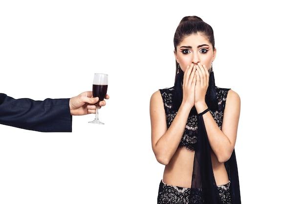 Männliche hand bietet einem jungen mädchen ein glas wein an. frau hat angst und will keinen alkohol trinken. isoliert auf weiß