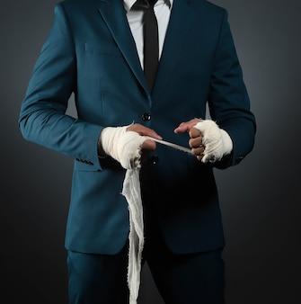 Männliche hand der nahaufnahme des geschäftsmannkämpfers im anzug mit verbänden und geballten fäusten.