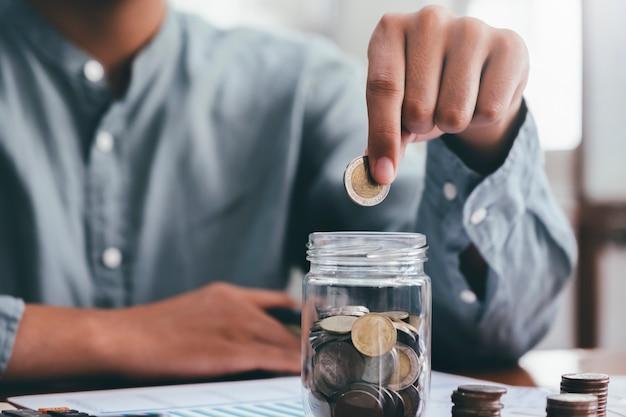 Männliche hand der nahaufnahme hält münzen, die in glas setzen.