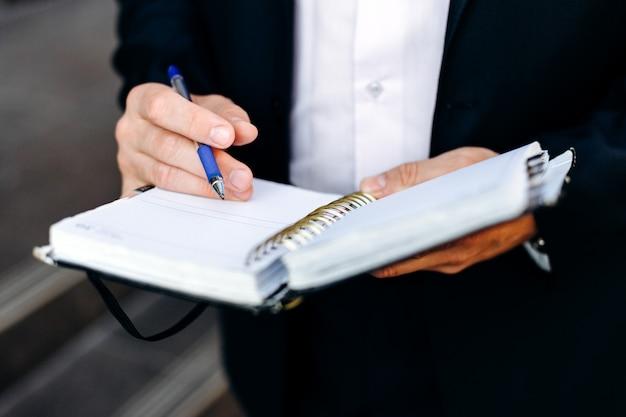 Männliche hand der nahaufnahme mit einem stift und einem notizbuch. hat eine notiz geschrieben.