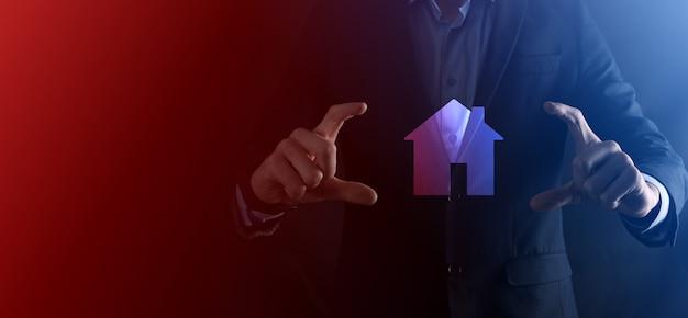 Männliche hand des geschäftsmannes, die hausikone auf blauem hintergrund hält. sachversicherung und sicherheitskonzept. immobilienkonzept. banner mit kopienraum.