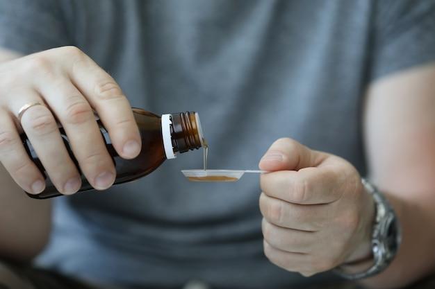 Männliche hand des mannes im krankenhaus gießt husten