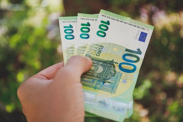 Männliche hand, die 100 hundert euro-banknoten auf grün hält