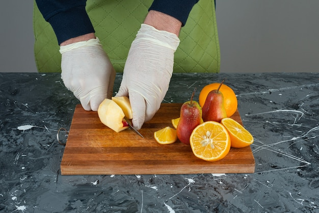 Männliche hand, die apfel mit messer oben auf holzbrett auf tisch schneidet.