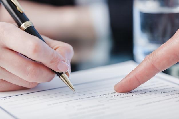 Männliche hand, die auf eine stelle zeigt, um ein papier zu unterschreiben