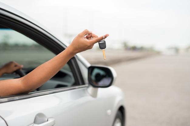 Männliche hand, die autoschlüssel beim sitzen im auto für neuwagenkonzept hält.