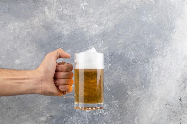 Männliche hand, die becher des kalten schaumigen bieres auf marmoroberfläche hält.