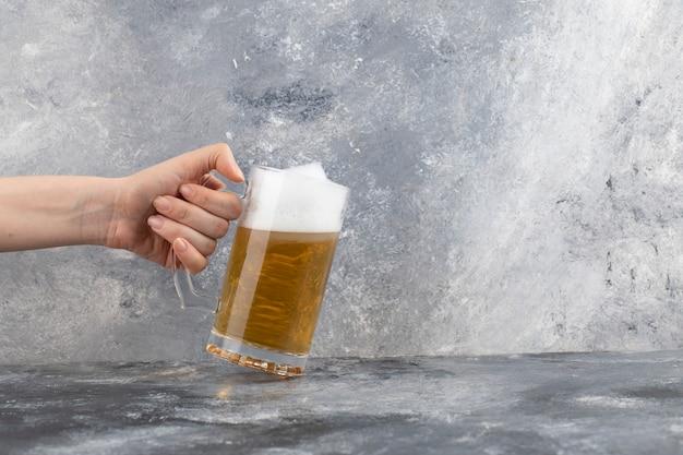 Männliche hand, die becher des kalten schaumigen bieres auf marmoroberfläche hält