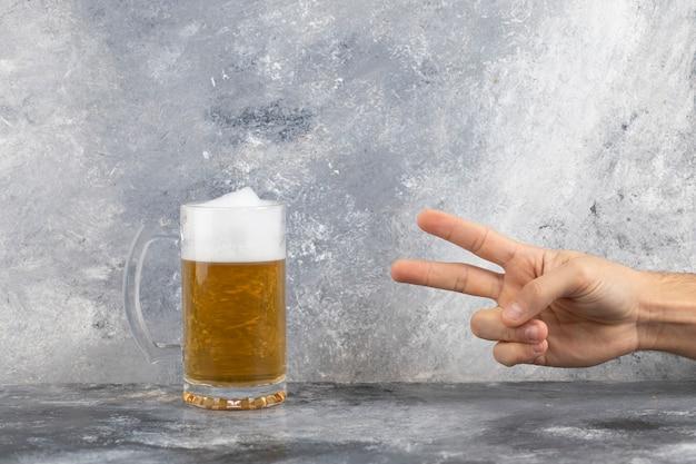 Männliche hand, die becher des kalten schaumigen bieres auf marmoroberfläche zeigt