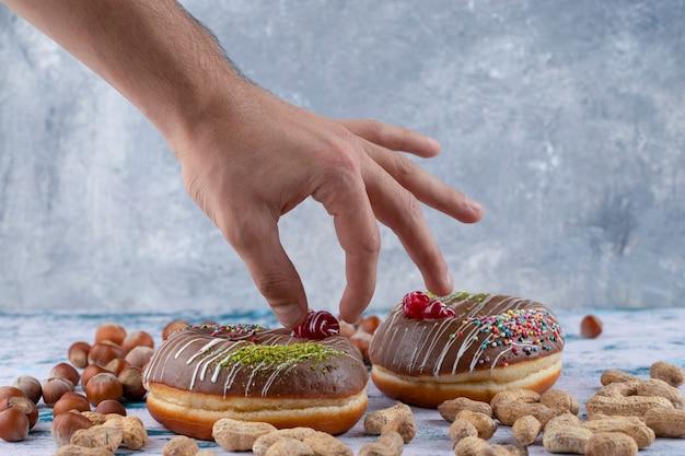 Männliche hand, die beere des schokoladenkrapfen nahe gesunden nüssen nimmt.