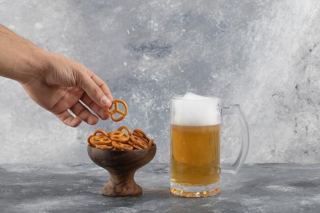 Männliche hand, die brezeln nahe becher des kalten schaumigen bieres auf marmoroberfläche hält