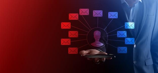 Männliche hand, die briefsymbol, e-mail-symbole hält. kontaktieren sie uns per newsletter-e-mail und schützen sie ihre persönlichen daten vor spam-mails. kundendienst-callcenter kontaktieren sie uns.e-mail-marketing und newsletter.