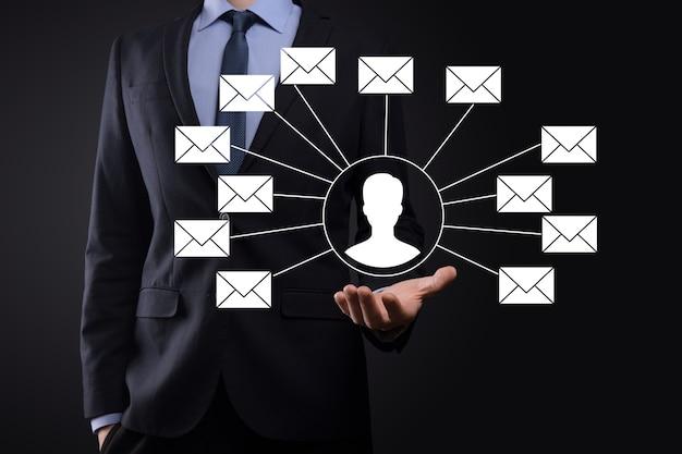 Männliche hand, die briefsymbol, e-mail-symbole hält. kontaktieren sie uns per newsletter-e-mail und schützen sie ihre persönlichen daten vor spam-mails. kundenservice-callcenter kontaktieren sie uns.e-mail-marketing und newsletter