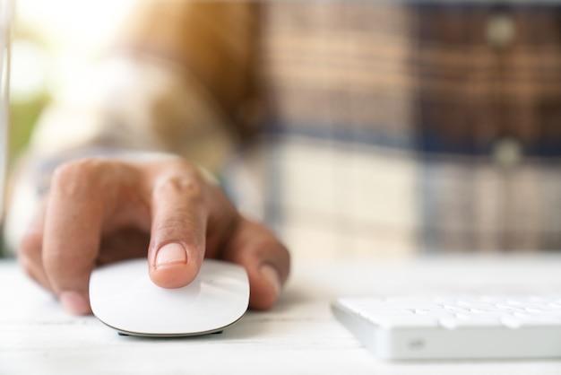 Männliche hand, die computermaus hält