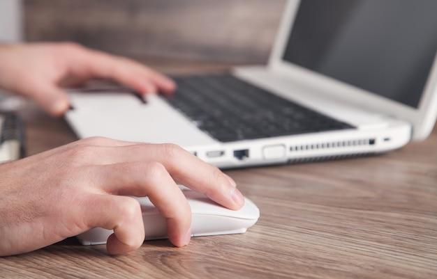 Männliche hand, die computermaus klickt