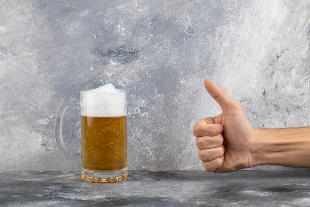 Männliche hand, die daumen nahe becher kaltes schaumiges bier auf marmoroberfläche aufgibt