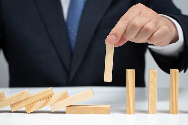 Männliche hand, die den dominoeffekt stoppt. risikokontrollkonzept.