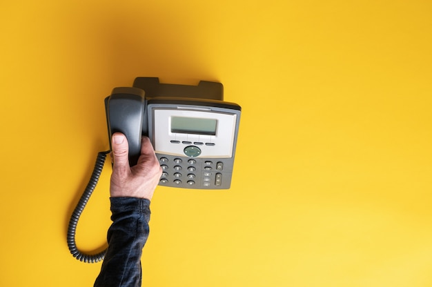 Männliche hand, die den telefonhörer eines schwarzen festnetztelefons abhebt