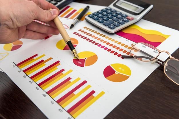 Männliche hand, die diagramm oder diagramm auf finanzbericht mit stift zeigt. wachstum und erfolg
